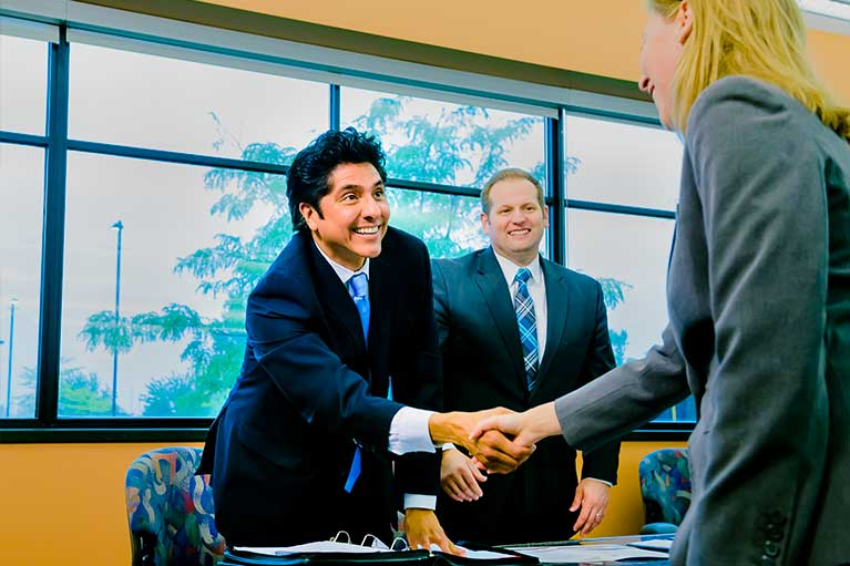 a man and woman shaking hands over a conference room table