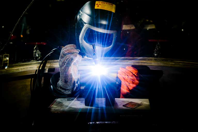 A person wearing protective equipment works on a welding project