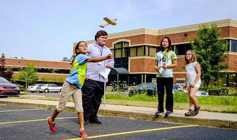 Children test out their miniature hand made airplane in the parking lot of LCC's East Campus