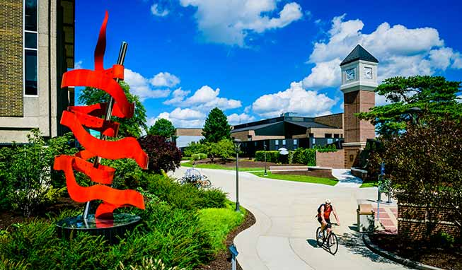 A man on a bike riding through campus with the Red Ribbon sculpture and clock tower in the background