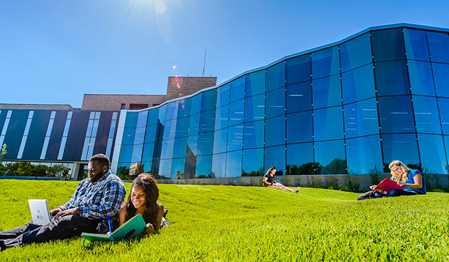 Students studying outside on the rolling lawn outside the Gannon glass