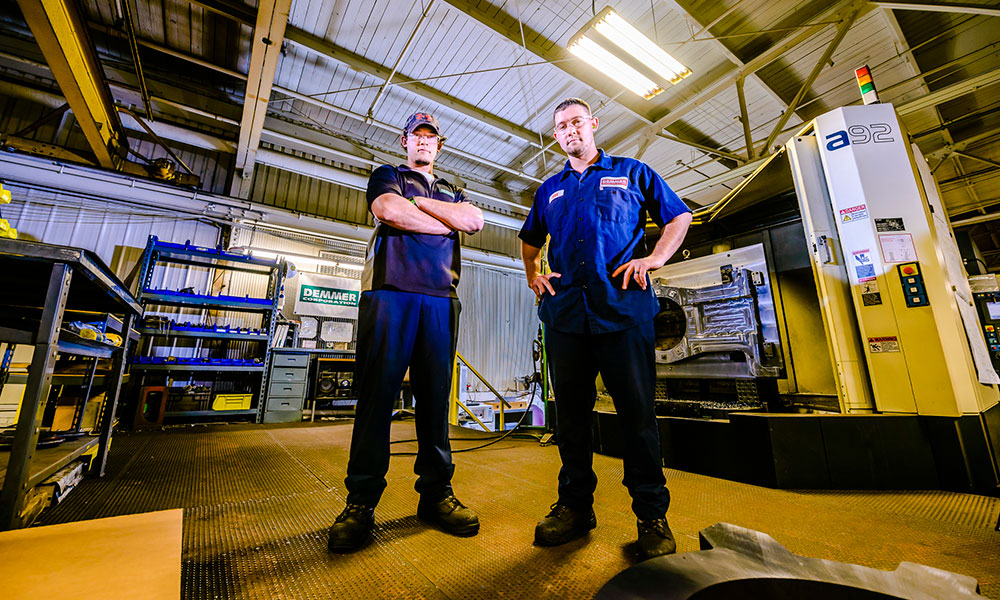 two apprenticeship students looking at the camera at a downward  angle with their arms crossed
