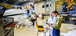 Together a student and instructor look at tools next to an airplane in the hangar at the Mason Jewett Airport
