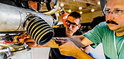 Instructor adjusts a bolt on exposed machinery as student watches
