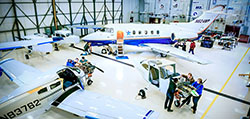 As viewed from above, small groups of students work on various aircraft inside the hanger at the Mason Jewett Airport