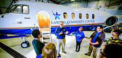 Teacher instructs group of students in front an LCC jet inside the hanger at the Mason Jewett Airport