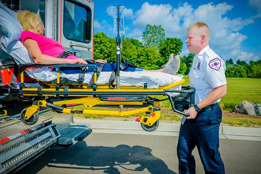 EMS Technician wheeling women on a stretcher up into an ambulance