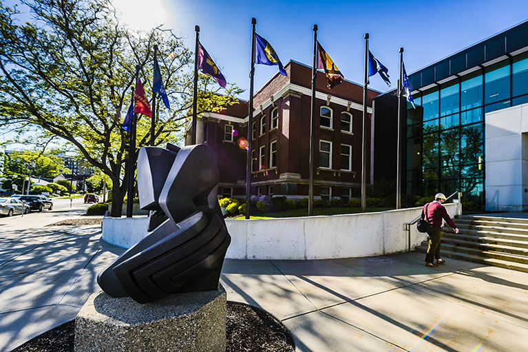 The flags of LCC's partnering universities fly outside the University Center entrance