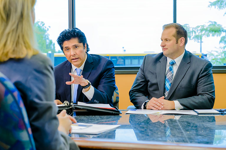 three people conversing business over a meeting room table