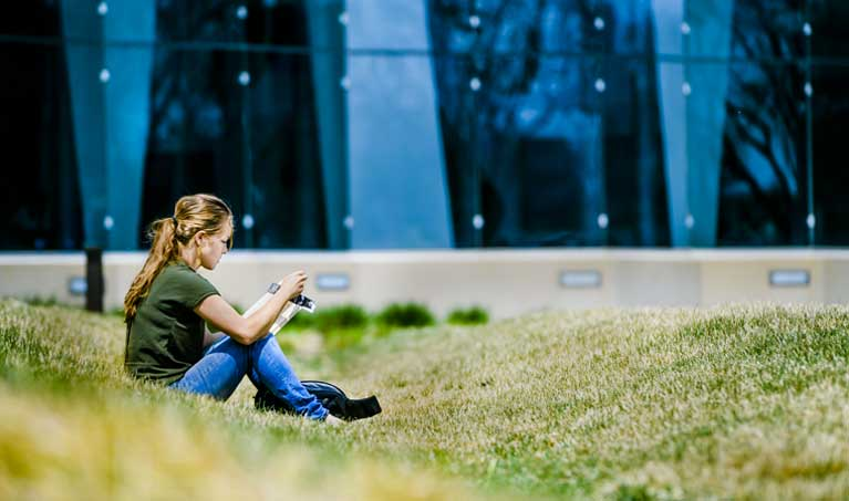 Woman sitting in the grass reading in front of the Gannon Building Glass