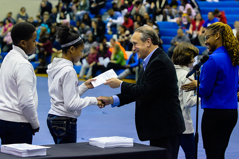 A highschool student accepts a certificate from LCC's President, Dr. Brent Knight