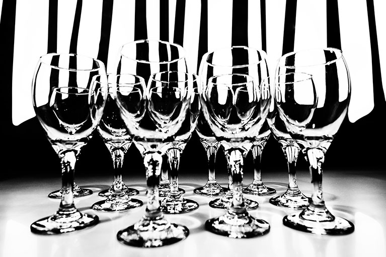 Wine glasses sit in a row