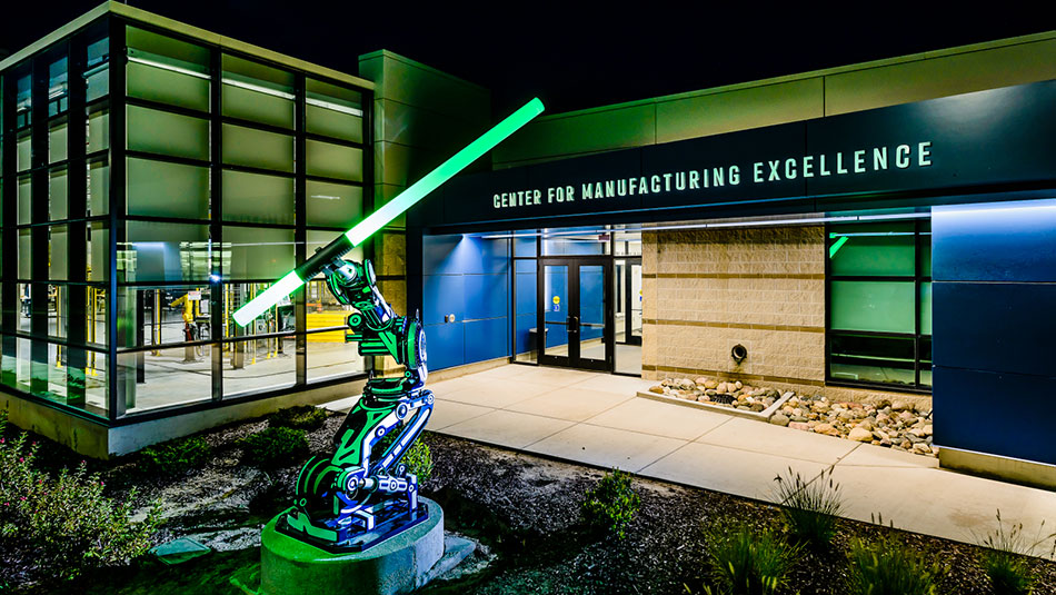 A glowing statue of a machine arm sits outside the Center for Manufacturing Excellence entrance
