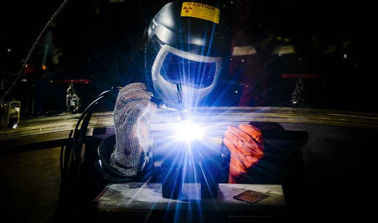 a student works on a welding project while wearing proper protection; sparks fly