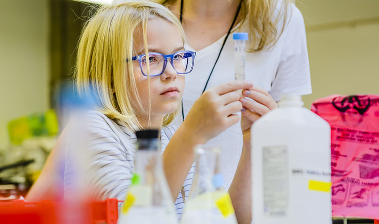 A young girl looks closely at a lidded test tube