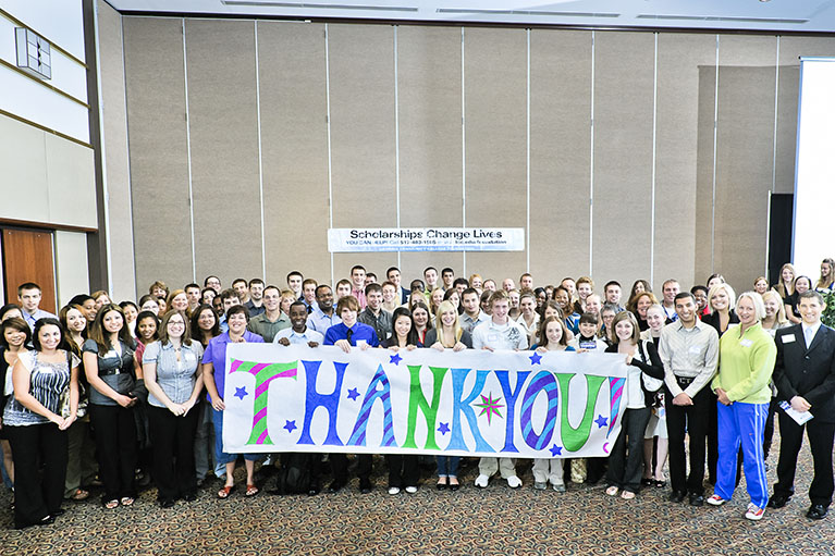 a large group of students who have received scholarships holding up a giant thank you banner