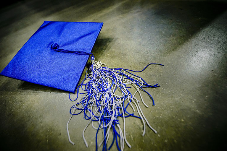 a blue LCC graduation cap on stone