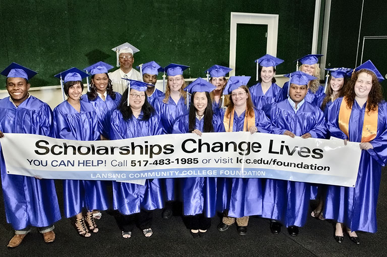 students who have received scholarships wearing their caps and gowns while holding up an advertisement banner for lcc scholarships