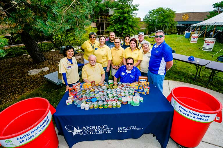 Employees in front of canned goods at employee development fund picnic