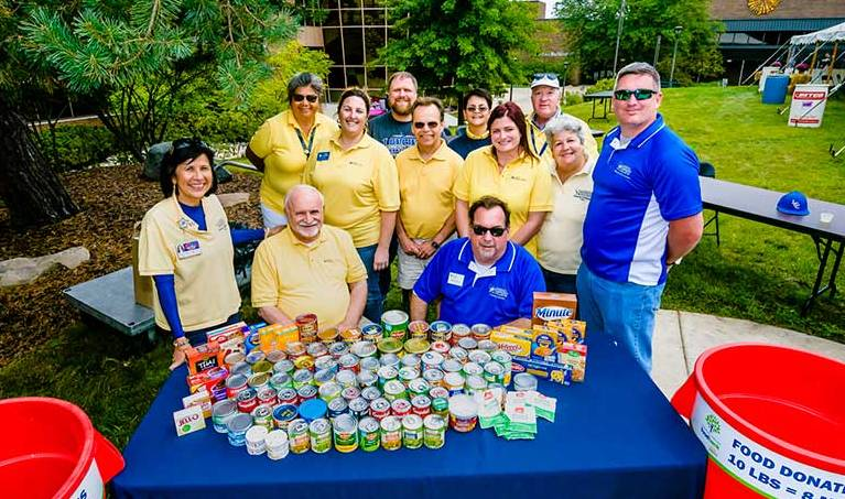 employees at a table with canned goods