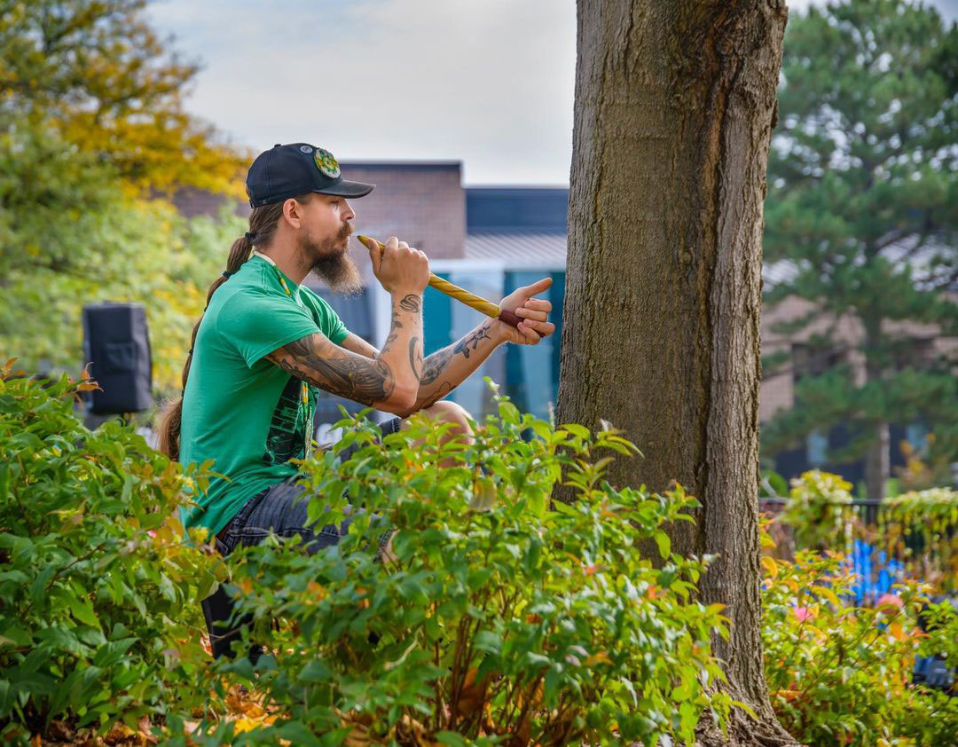 man playing an instrument outside next to a tree on lcc campus