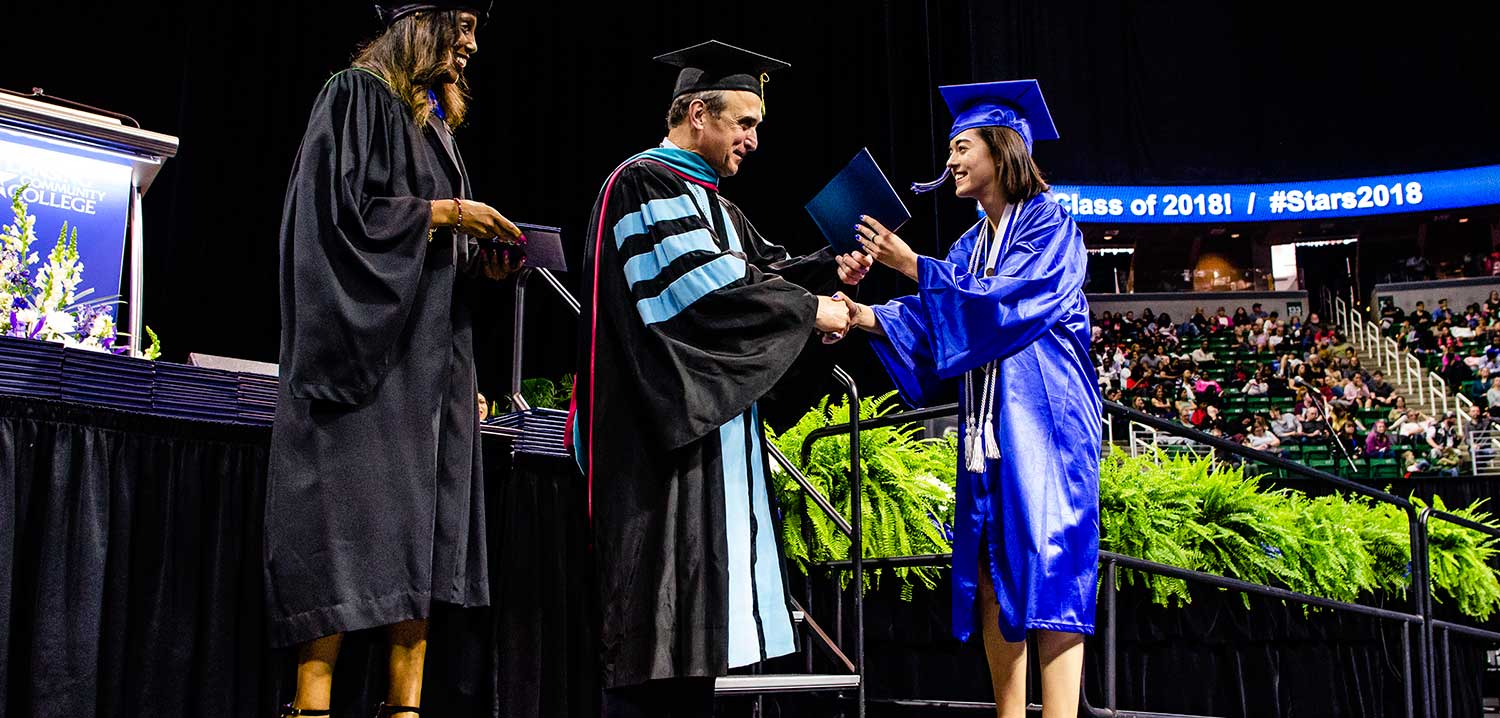 Woman shaking hands with Dr. Knight as she receives her degree