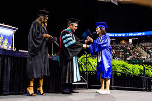 Woman shaking hands with Dr. Knight as she receives her diploma on stage