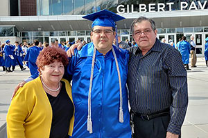 Hansel Valdés standing with his parents after graduation