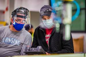 robotics student and instructor with masks on their faces