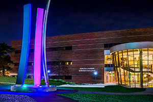 Upward Bound sculpture at night with HHS building in the background