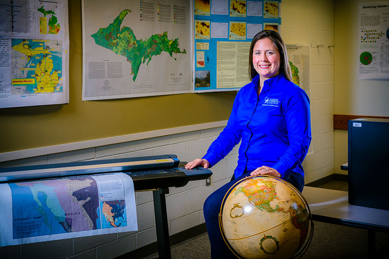 LCC Geography instructor posing with a globe for a photo in a classroom