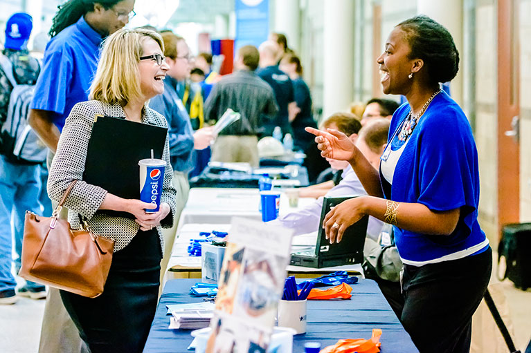 Two women talking at a past job fair event