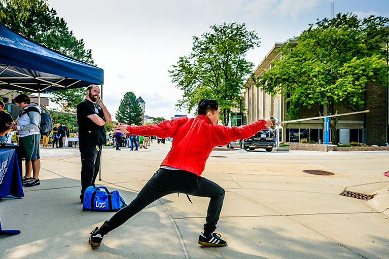 Student demonstrates fencing stance on the Washington Mall