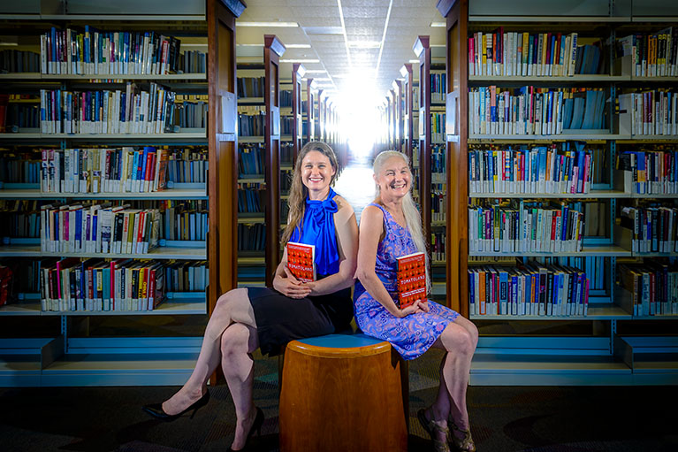 Librarians sit together among rows of books