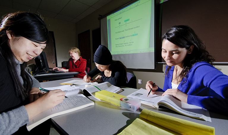 Three students sit around a table in a class room studying textbooks