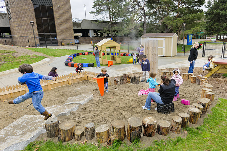 Children play outside as teachers watch at the ELCC