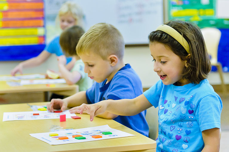 Children in a classroom count shapes