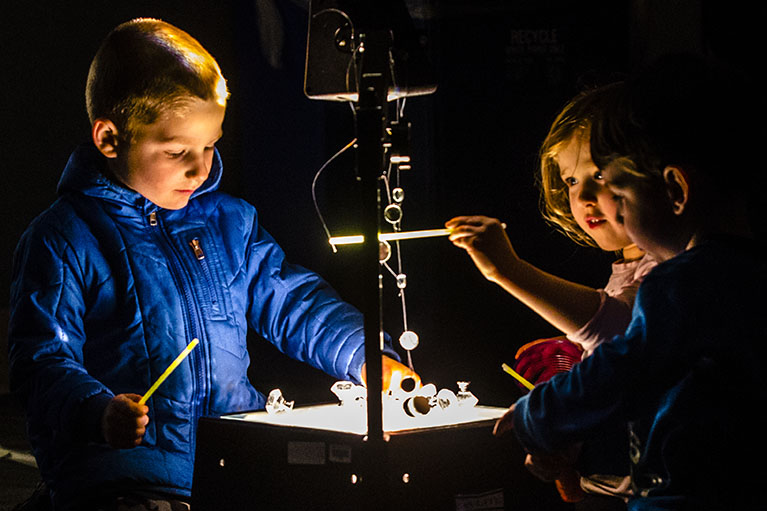 Children play with shapes on an overhead projector