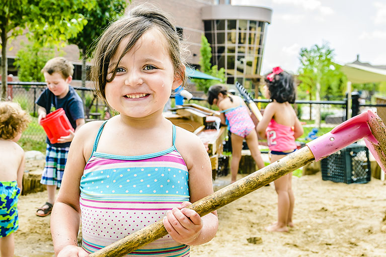 In the ELCC outside play area, a small girl holds a shovel covered in sand