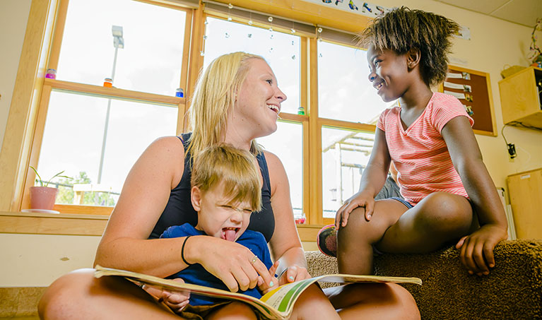 Teacher reads a book to two children who grin and make a silly face