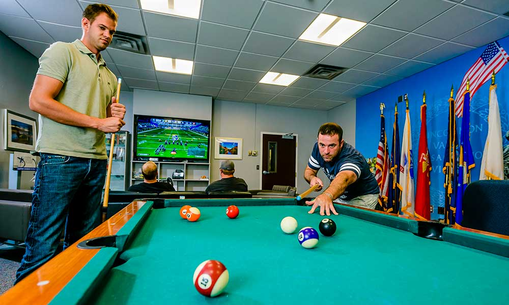 two veteran students playing pool
