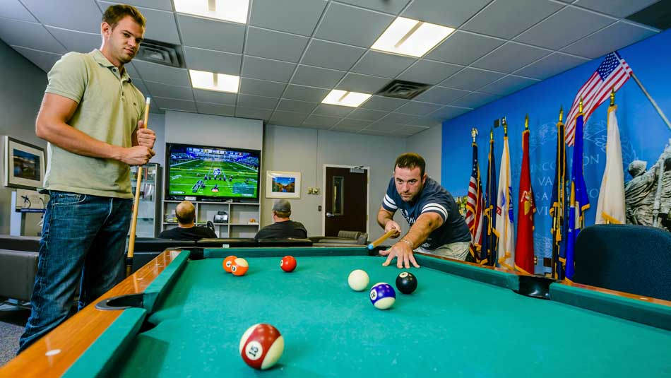 Students play pool and video games in the VRC lounge