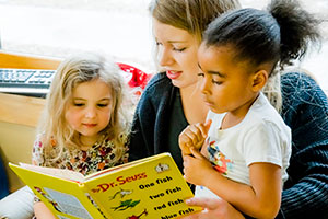 Child Care worker reading to young kids