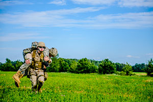 One military carrying another through a grassy field